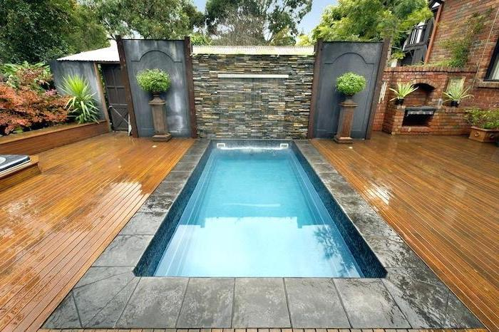 small pool with a fountain, surrounded by cement tiles, small backyard ideas, potted plants, planted bushes