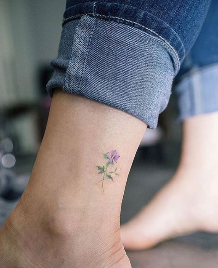 small flower ankle tattoo, cool small tattoos for guys, person wearing jeans, with bare feet