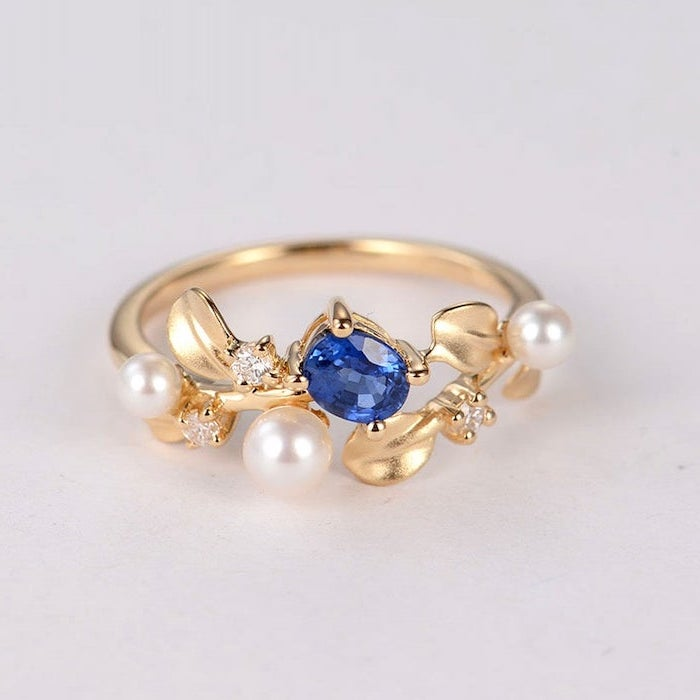 golden band with pearls, non traditional wedding rings, small sapphire stone in the middle