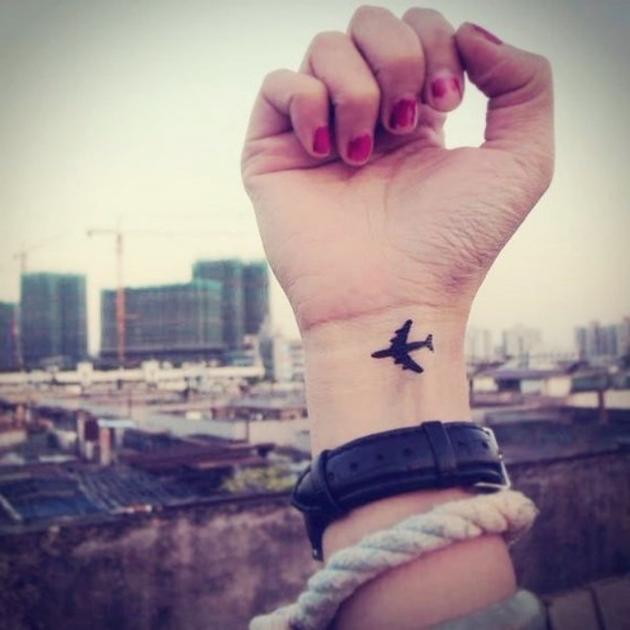small black airplane wrist tattoo, small forearm tattoo, city landscape in the background