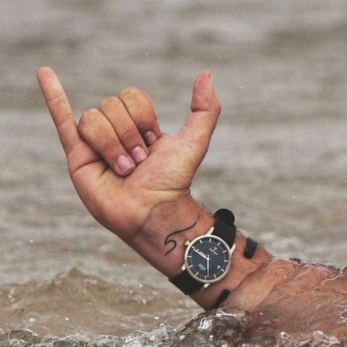 small wave wrist tattoo, small forearm tattoo, hand coming out of water, wearing a black watch