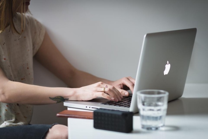 woman sitting down, typing on a macbook, leaves wrist tattoo, small lotus flower tattoo