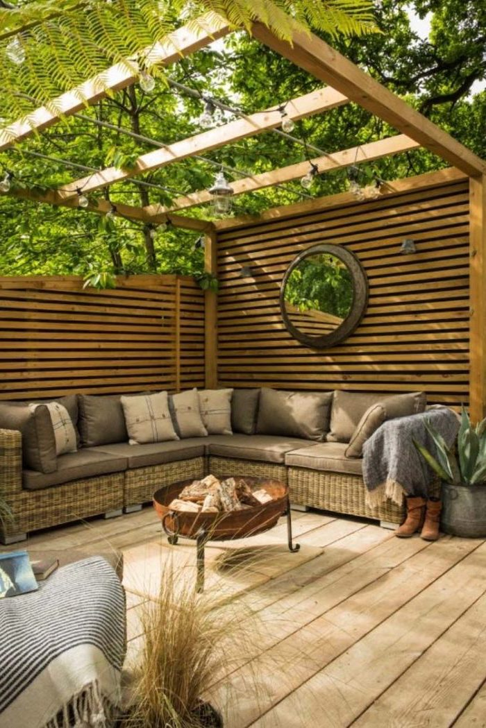 wooden shed, garden furniture, with colourful throw pillows, underneath it, on a wooden floor, small yard landscaping