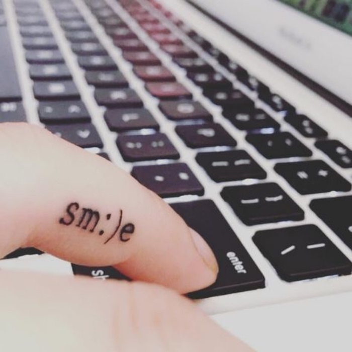 smile finger tattoo, person typing on a macbook keyboard, small lotus flower tattoo