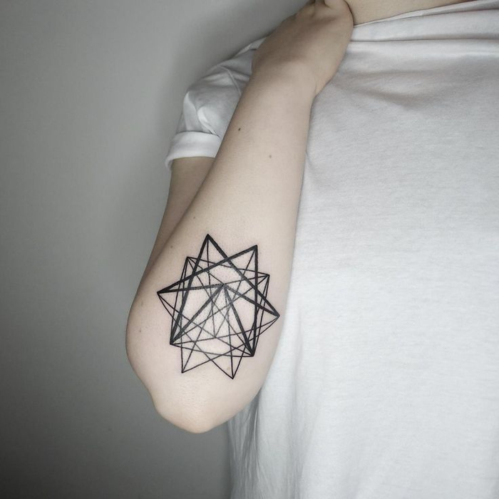 geometric tattoo, geometrical star, under the elbow, person dress in white shirt, standing in front of a white background