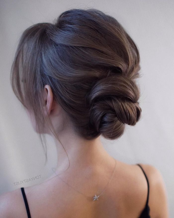 wedding hairstyles for medium hair, brown hair in a low updo, black straps, star necklace, white background
