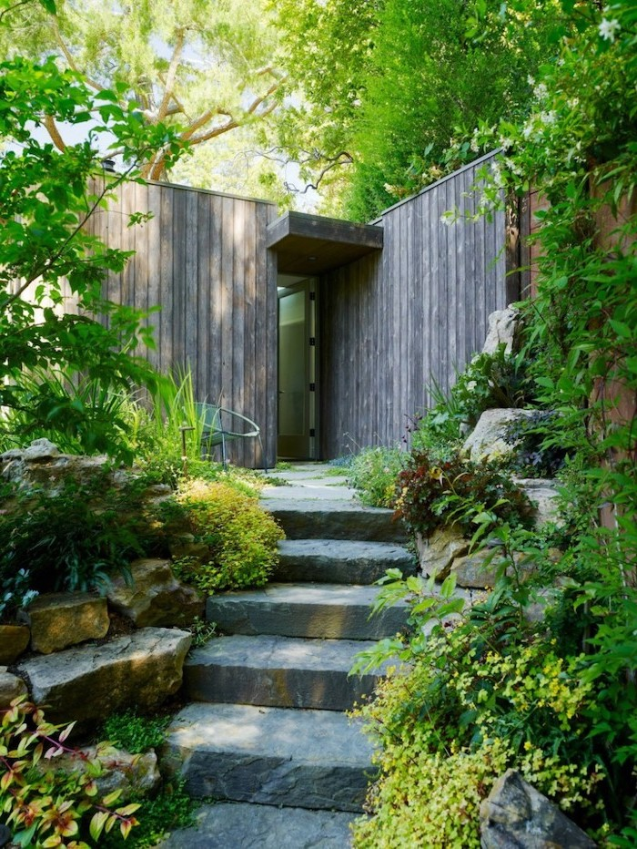 stone pathway, planted bushes flowers and trees alongside it, small yard landscaping, wooden entrance