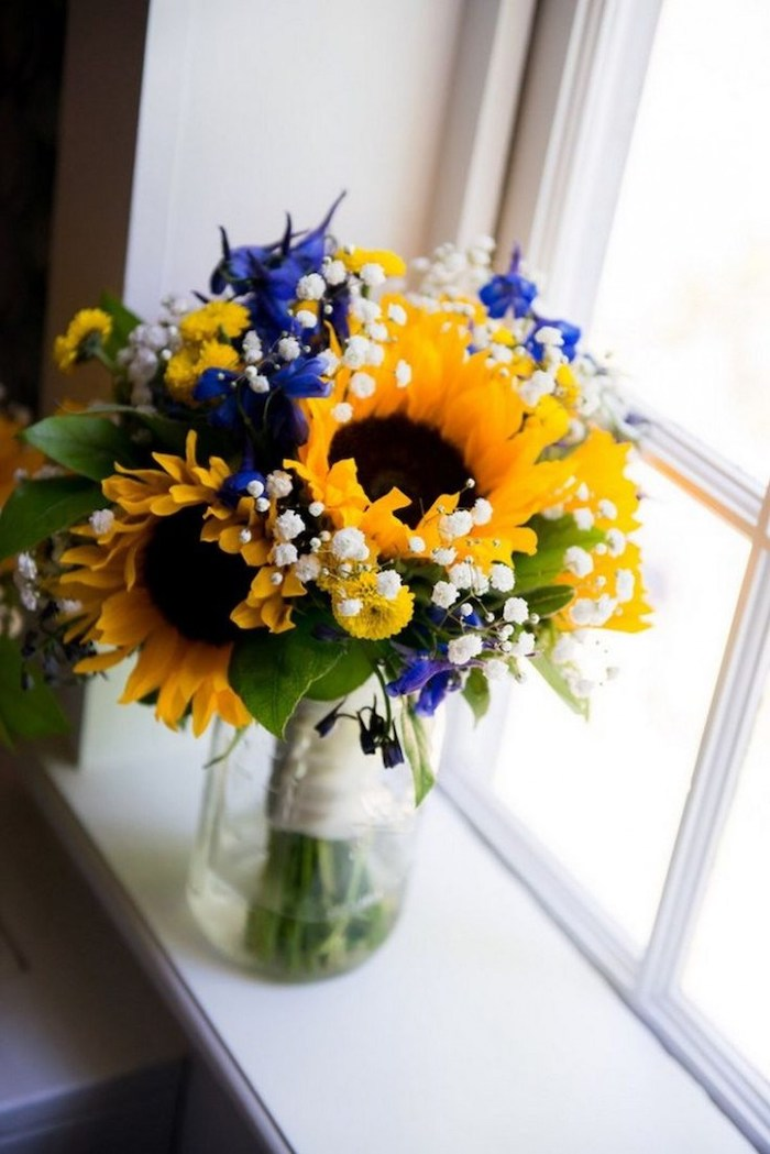 sunflowers and blue flowers, small flower bouquet, in a glass round vase, in front of a window, flower arrangement pictures
