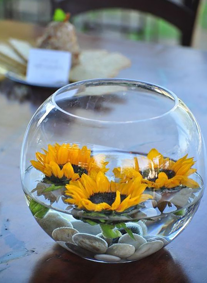 small round glass vase, sunflowers and river stones, floating in it, flower arrangement pictures, on a wooden table