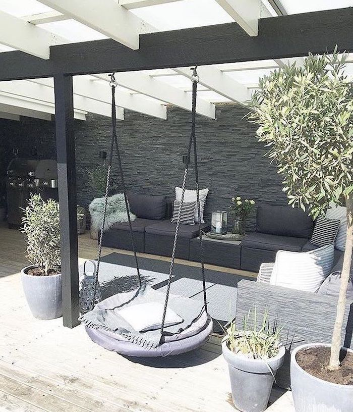 swing hanging from the ceiling, garden furniture, with colourful throw pillows, small yard landscaping ideas