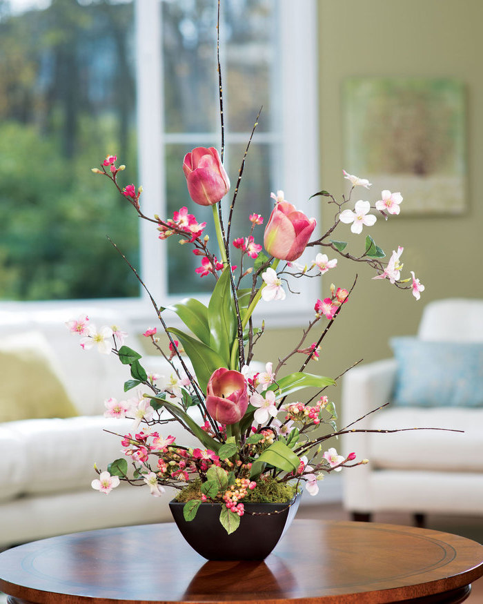 silk flower arrangements, pink tulips, small magnolias, in a small pot with moss, on a round wooden table