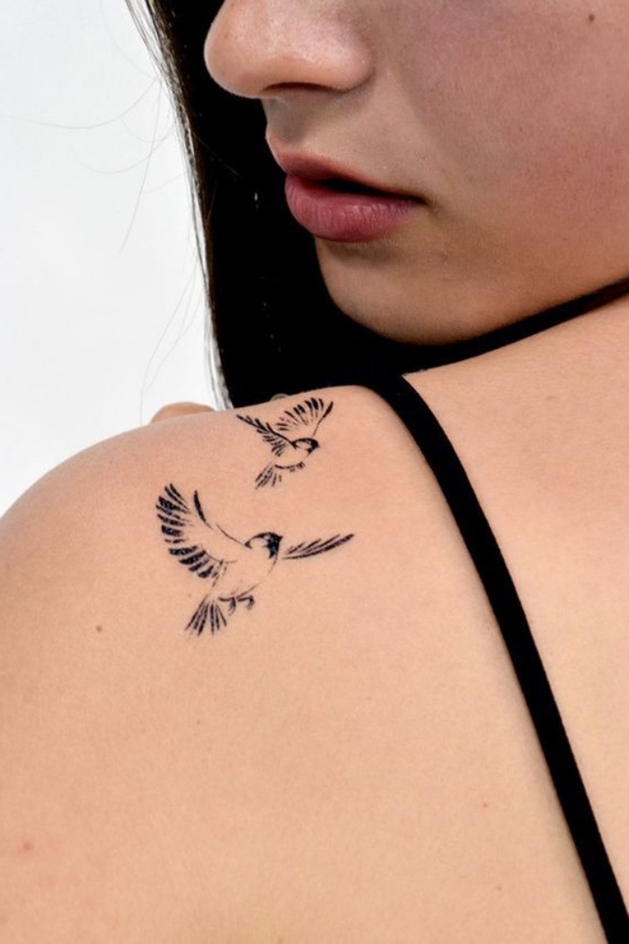 two birds flying away shoulder tattoo, woman with long black hair, small matching tattoos, black straps