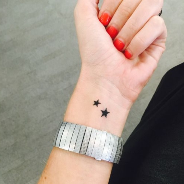 best small tattoos for men, two black stars wrist tattoo, large silver bracelet, red nail polish