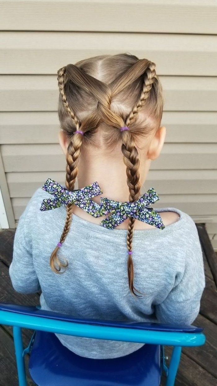 two crossed braids, two floral bows, cute simple hairstyles, blonde hair, blue chair, grey blouse