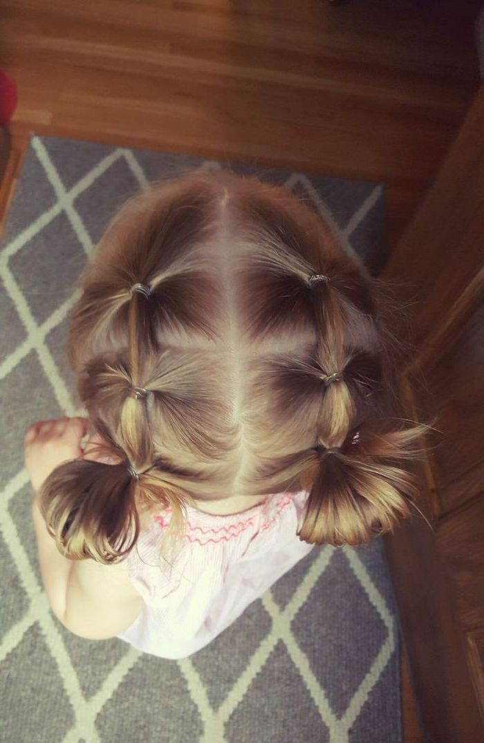 easy hairstyles to do yourself, two braids ending in small buns, grey carpet, blonde hair