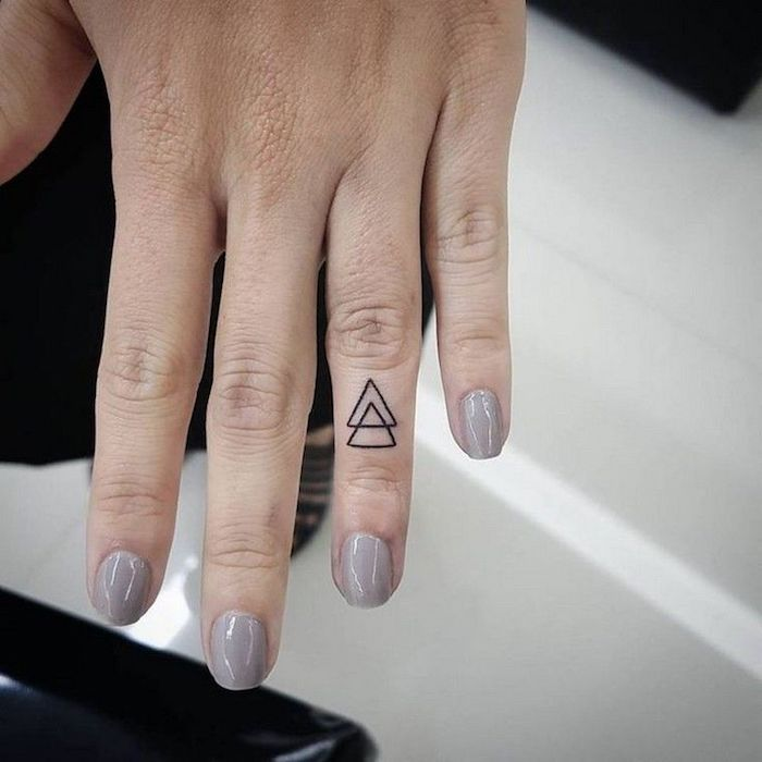 two intertwined triangles, on the ring finger, finger tattoo, hand with grey nail polish