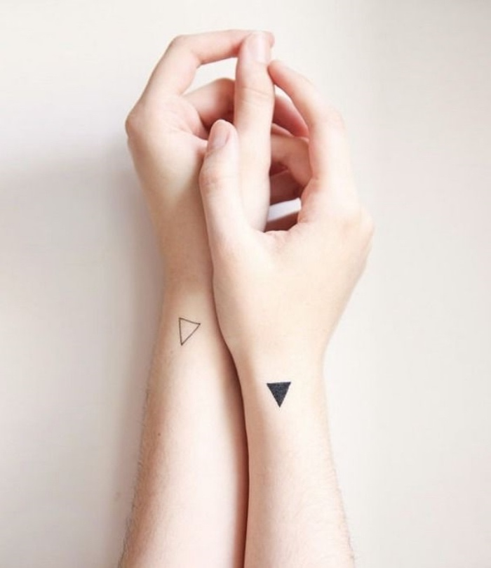 white and black triangle wrist tattoos, on both hands, best small tattoos for men, hands in front of a white background
