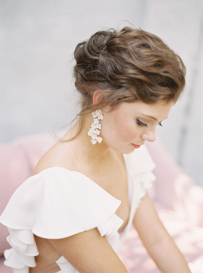 brown wavy hair, in a low updo, long earrings, wedding hairstyles for medium hair, white dress