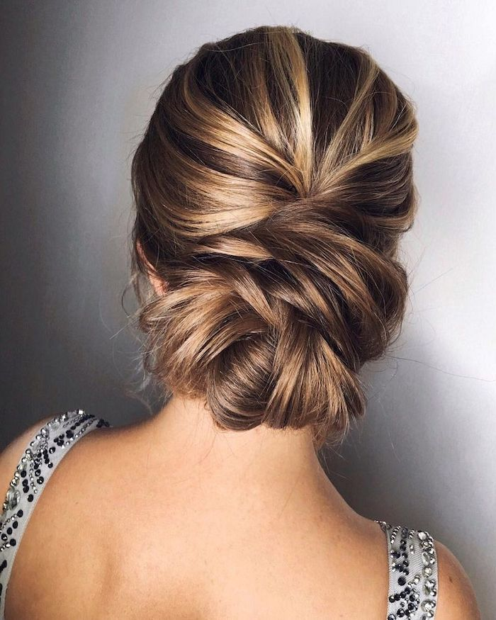 brown hair with highlights, loose updos, in a low updo, grey background, grey dress straps