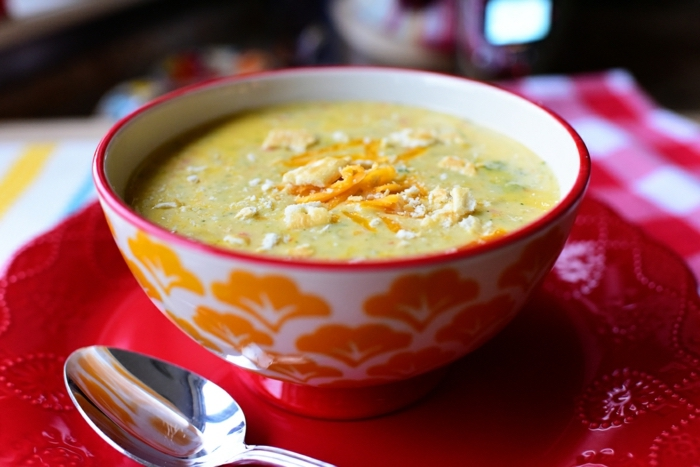 cream soup with carrots, inside a white and orange bowl, on a red plate, healthy eating plan