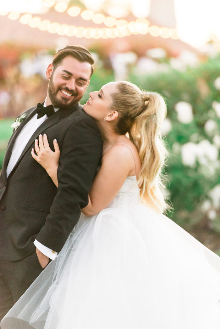 long white dress, long blonde hair, in a high ponytail, bridesmaid hairstyles, woman hugging a man, in a tuxedo