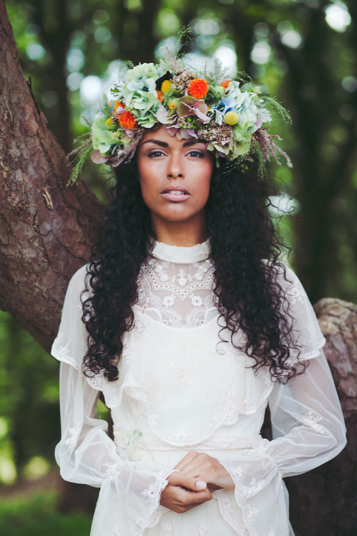 white lace dress, very curly black hair, wedding updos for long hair, large floral crown