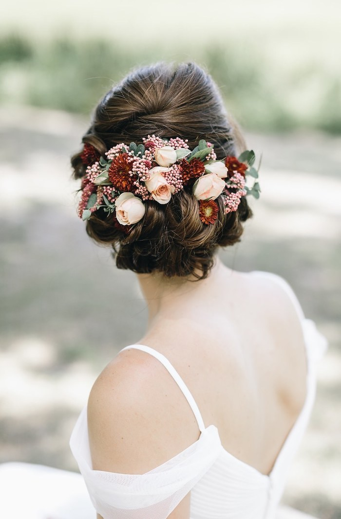 bridesmaid hairstyles, brown hair in a low updo, flower hair accessory, white dress