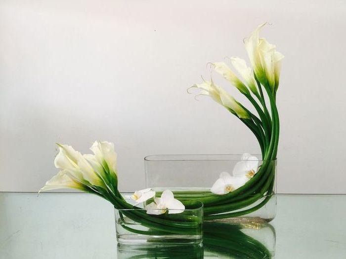 white flowers, in a bathtub like vases, flower art, flower arrangements ideas, on a glass countertop