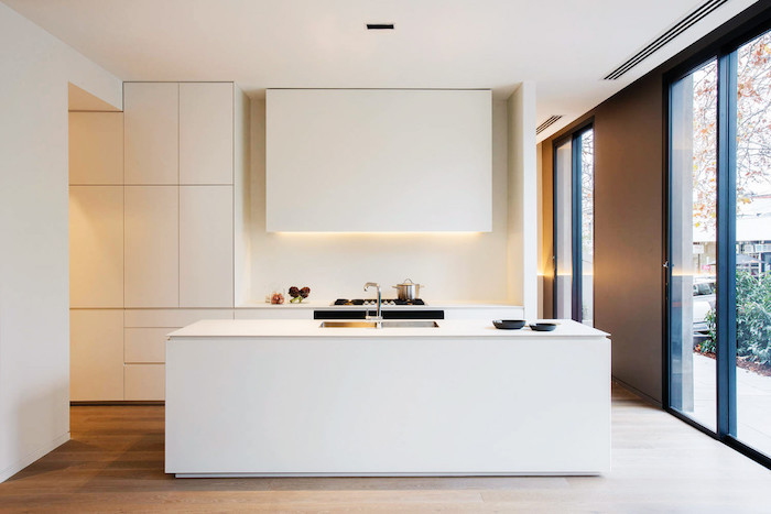 white minimalistic kitchen, white kitchen island in the middle, kitchen appliances, white cupboards and drawers, large windows