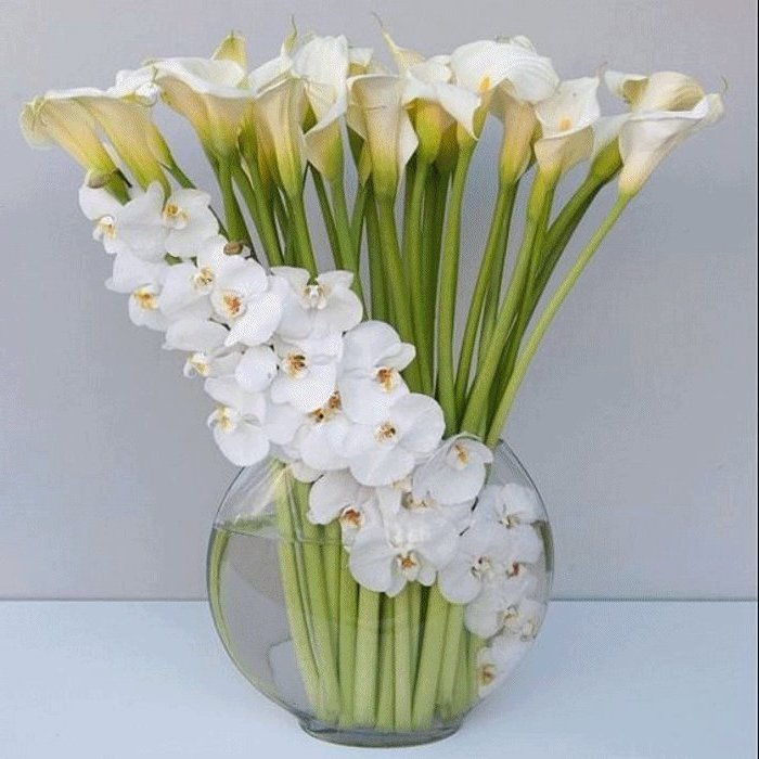 white lilies and magnolias, in a large round glass vase, on a white countertop, flower arrangements ideas