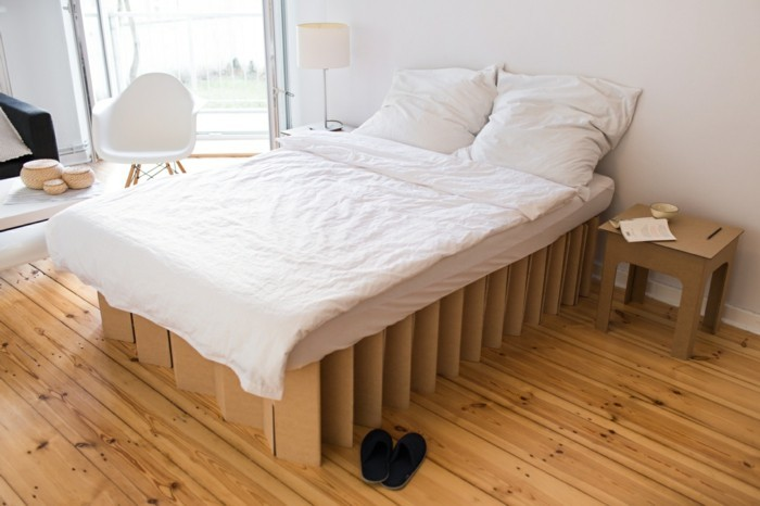 cardboard bed, with white linens, on a wooden floor, with a cardboard nightstand, cardboard chair