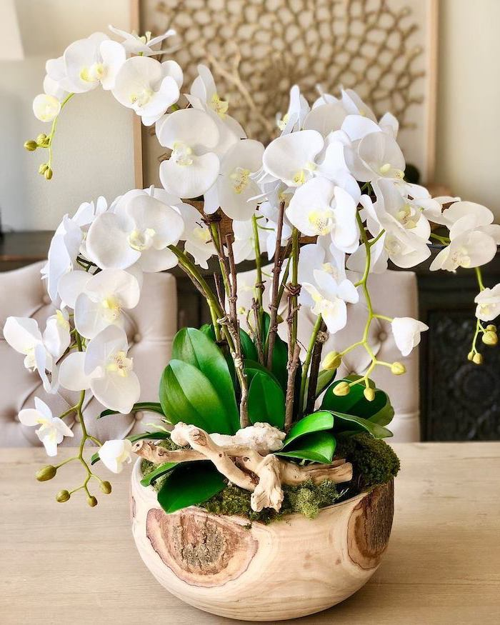 white orchids, in a wooden pot, with moss in it, mason jar flower arrangements, on a wooden table