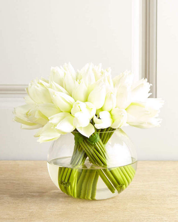 white tulips, in a glass round vase, mason jar flower arrangements, on a wooden table, in front of a white wall