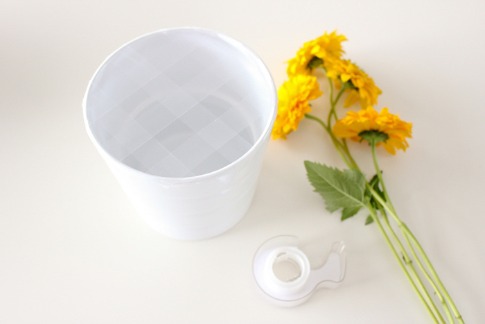 yellow flowers and tape, on a white countertop, flower centerpieces, white vase with tape on it