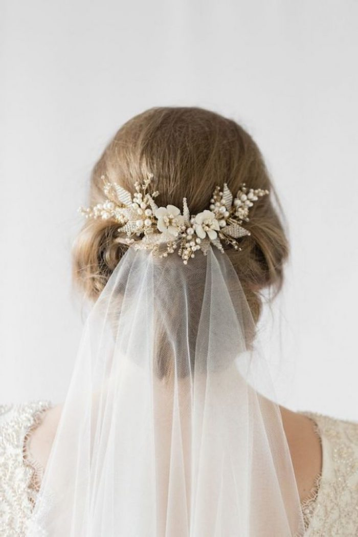 white veil, with a floral hair clip, blonde hair in a low updo, bridesmaid hairstyles, white background