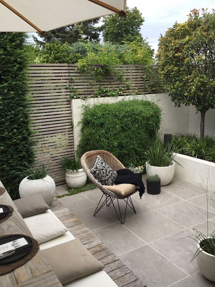 small lounge chair with a throw pillow and blanket, small backyard ideas, planted trees and bushes, cement tiled floor