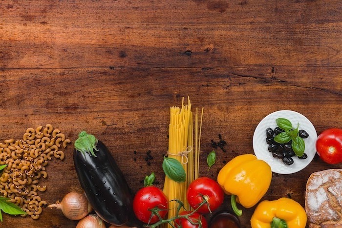 wooden countertop, healthy meal plans for women, aubergine and onions, peppers and tomatoes, olives and pasta