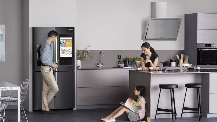 black and grey stainless steel kitchen appliances, two black bar stools, white and beige walls