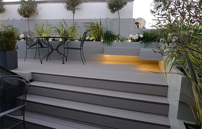 small space gardening, black metal garden furniture, surrounded by planted bushes trees and flowers