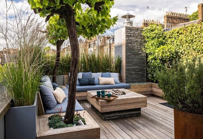 wooden garden furniture, with colourful throw pillows, planted trees and bushes, small patio ideas
