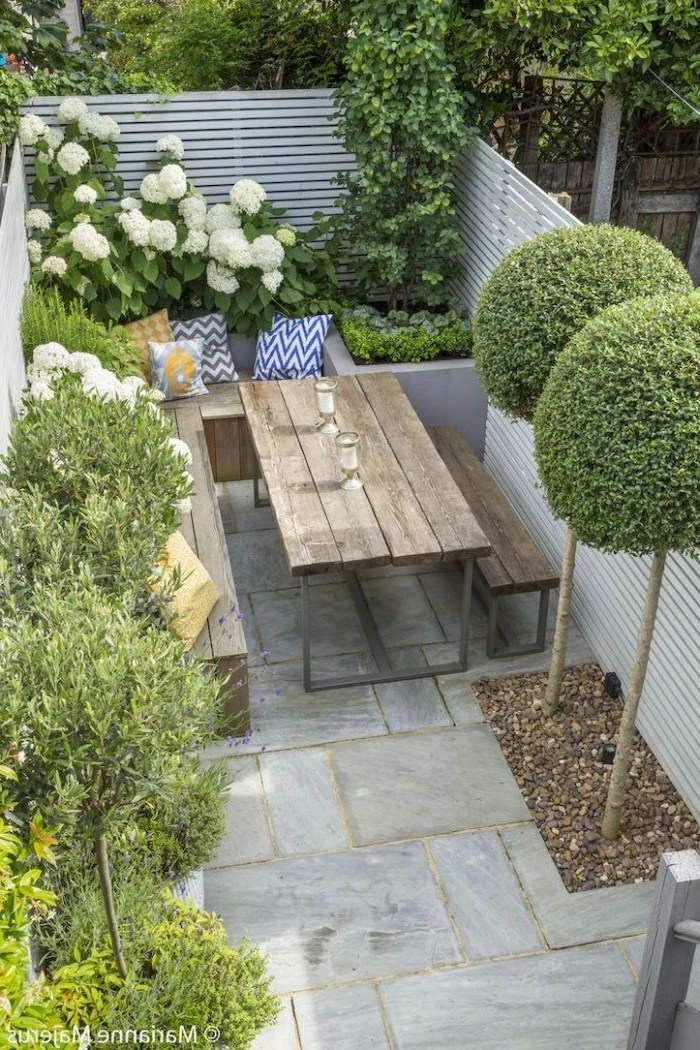 wooden garden furniture, planted trees bushes and flowers, small patio ideas, cement tiled floor