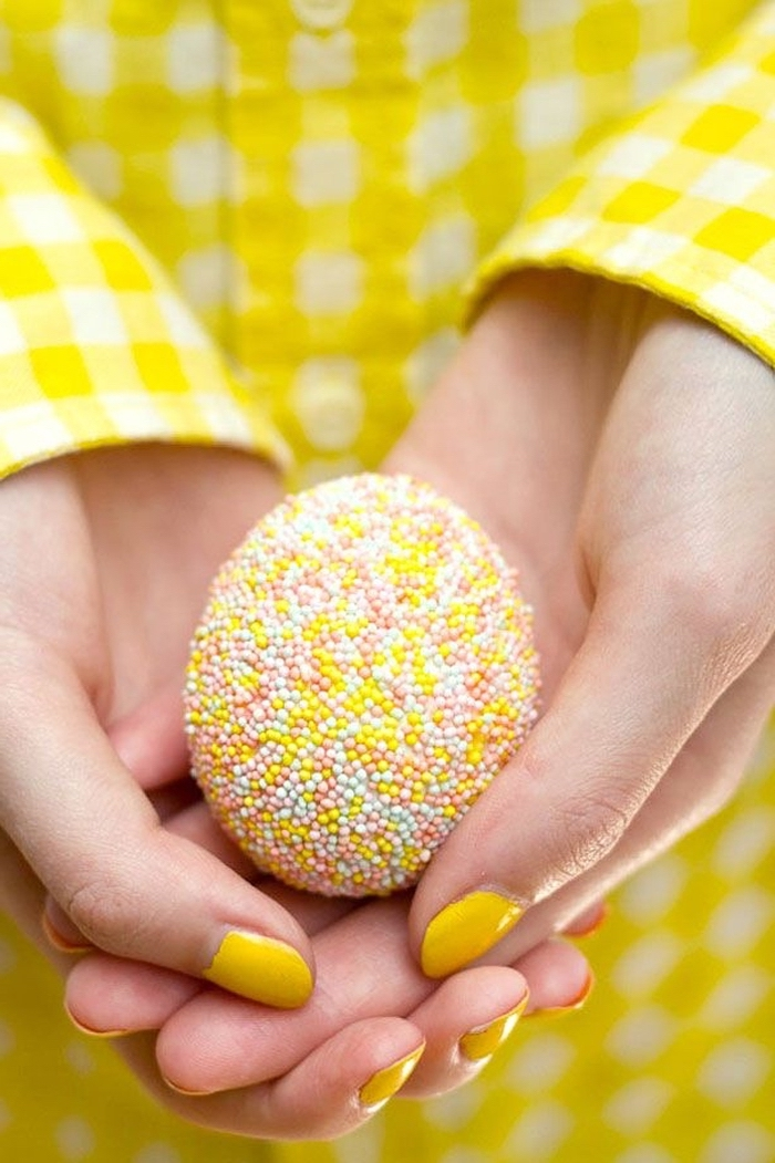 hand with yellow nail polish, wearing a yellow plaid shirt, holding a sprinkled egg, how to color easter eggs
