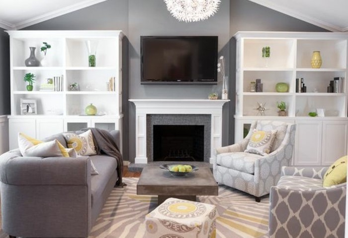 white bookshelves, grey couch living room, white and grey armchairs, yellow accents around the room