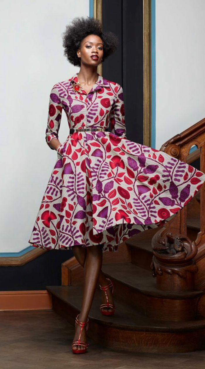 woman standing on a wooden staircase, wearing a mid length dress, red high heel sandals, african print