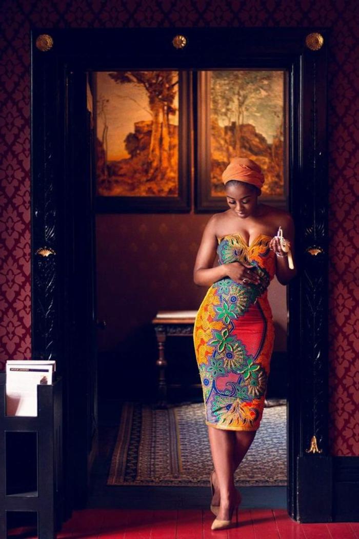woman standing in the doorway, wearing a dress, african print, orange headscarf. nude heels