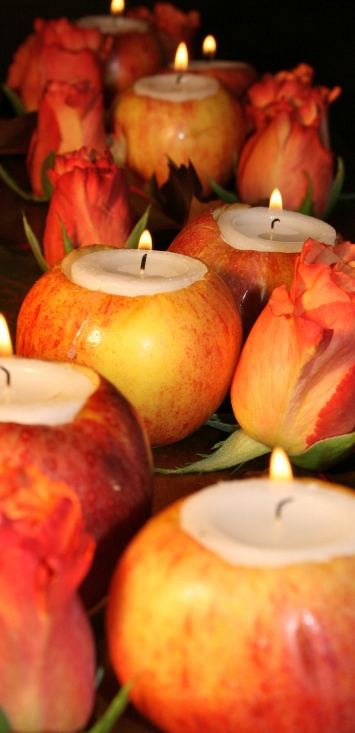 emptied apples, filled with candles, red tulips, surrounding them, table setting ideas