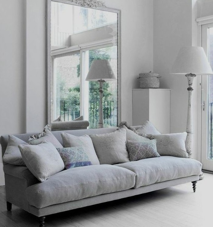 large mirror, grey couch living room, grey throw pillows, white walls, wooden floor
