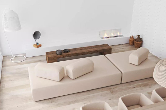 minimalist living room, electric fireplace, nude sofa, wooden floor, wooden bench, coffee table