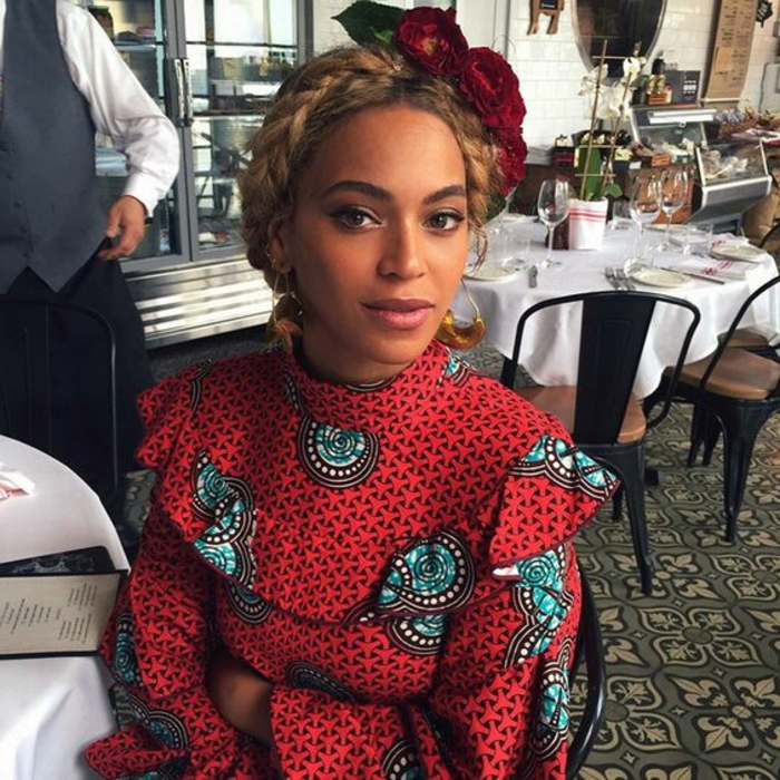 beyonce sitting down, wearing a glower wreath headband, african dresses, patterned top, braided hair