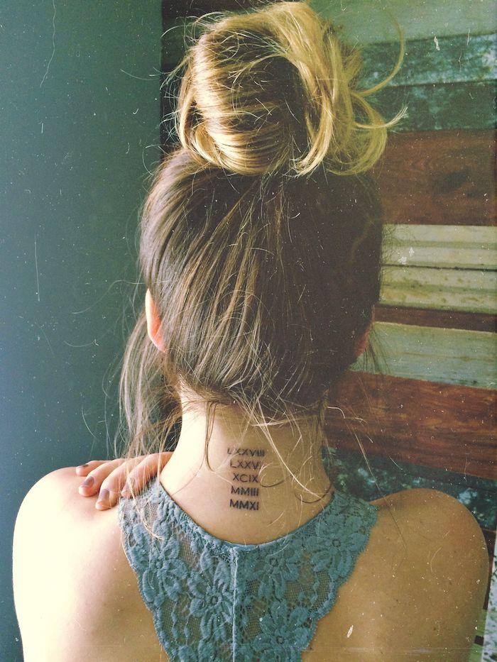 blonde hair in a messy bun, blue lace top, back tattoo, roman numerals, blue backgorund